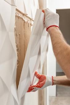 Instalación de panel de yeso 3d. un trabajador fija la loseta de yeso a la pared.