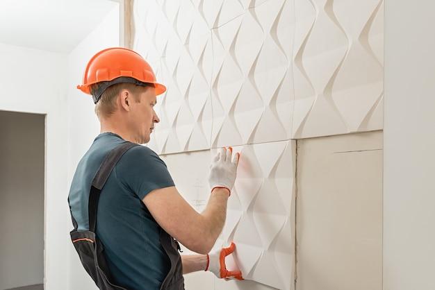 Instalación de panel de yeso 3d. el trabajador está pegando la loseta de yeso a la pared.
