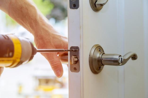 La instalación de las perillas de las puertas interiores bloqueadas, las manos de los carpinteros de cerca instala la cerradura.