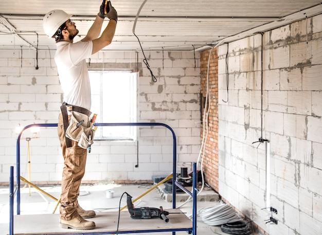 Instalador electricista con una herramienta en sus manos, trabajando con cable en el sitio de construcción