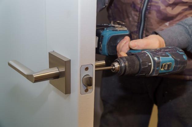 Instale la manija de la puerta con una cerradura, carpenter apriete el tornillo, usando un taladro eléctrico