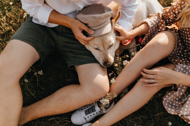 Instantánea de hombre y mujer en trajes de verano poniendo gorra beige en labrador retriever.