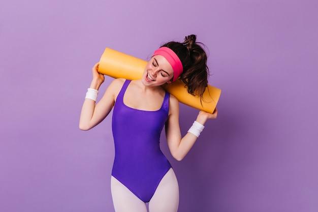 Instantánea de mujer atractiva en ropa deportiva al estilo de los años 80, posando con estera de aeróbic en la pared púrpura