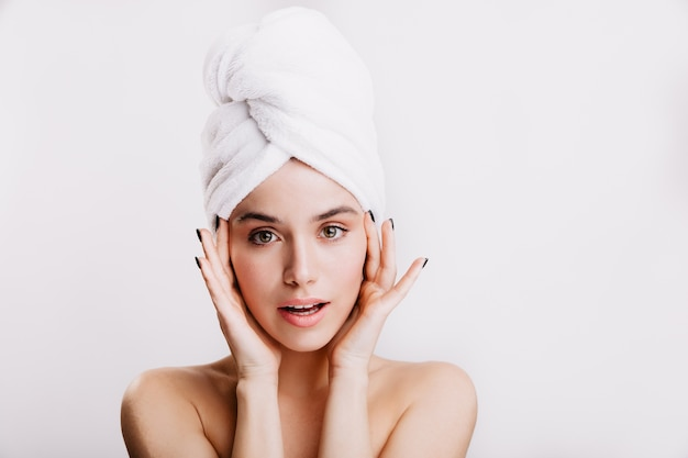 Instantánea de niña hermosa sana en toalla blanca en la cabeza. mujer de ojos verdes toca su rostro.