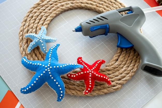 Instrucciones de bricolaje tutorial paso a paso cómo hacer una corona de cuerda decorativa de verano con estrellas de mar hecha de fieltro herramientas y suministros para manualidades