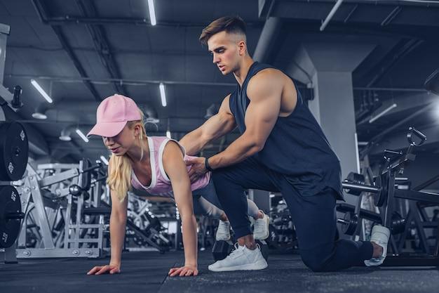 Instructor de acondicionamiento físico que ayuda a hacer flexiones en el entrenamiento en el gimnasio