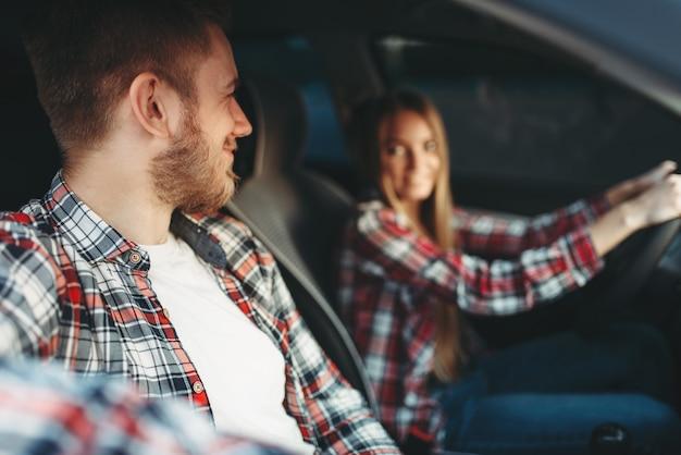 Instructor y alumna sonriendo en vehículo