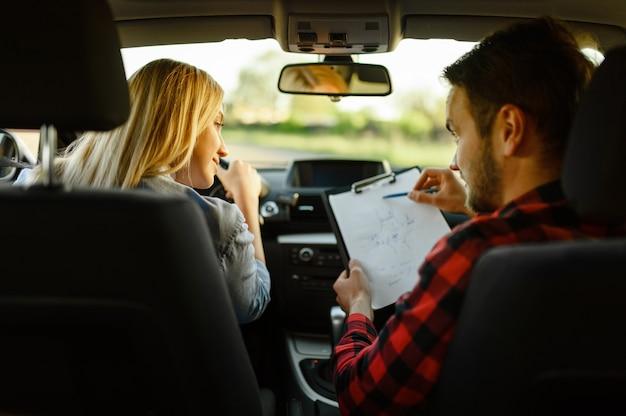El instructor ayuda a la mujer a conducir el coche.