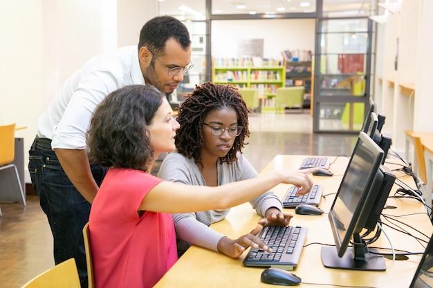 Instructor ayudando a estudiantes en clase de computación