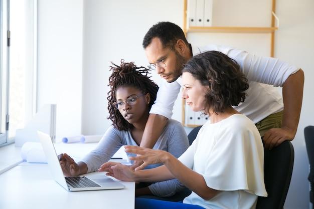Instructor ayudando a nuevos empleados con software corporativo