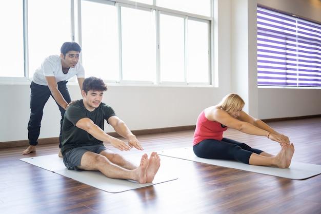 Instructor ayudando a los principiantes a hacer la postura hacia adelante.