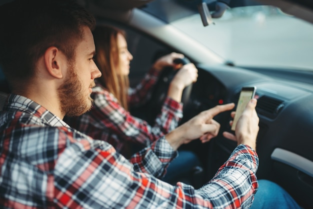 Instructor de conducción muestra el camino a la estudiante