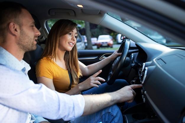 Instructor de conducción que muestra el tablero y los botones del vehículo al estudiante que toma lecciones de conducción