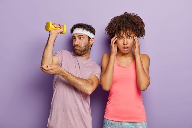 Instructor deportivo masculino hace ejercicios con mancuernas, trabaja para tener bíceps, trata de levantar objetos pesados, usa diadema y camiseta, el aprendiz femenino se para cerca, masajea las sienes, cansado después del entrenamiento