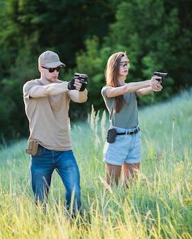 El instructor le enseña a la niña a disparar una pistola al campo