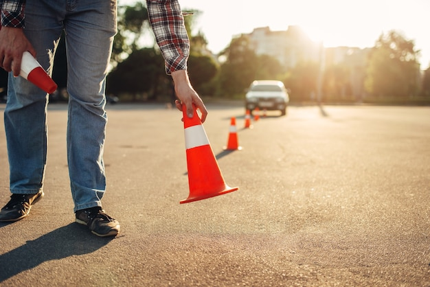 Instructor establece el cono, concepto de escuela de conducción