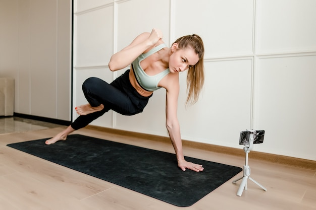 Instructor de fitness que graba entrenamiento deportivo en vivo por teléfono para clientes en línea en casa