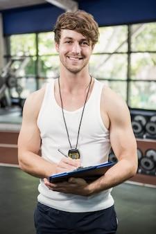 Instructor de gimnasia escribiendo en portapapeles