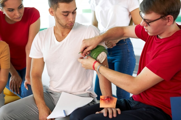 El instructor masculino profesional usa un torniquete para prevenir el sangrado durante el entrenamiento de primeros auxilios