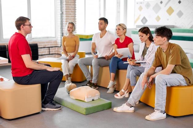 Instructor masculino seguro muestra y habla sobre la primera rcp de emergencia