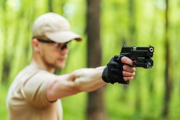 Instructor con pistola en bosque conduce apuntando y posando