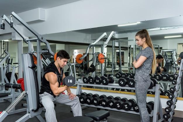 Instructor que trabaja con el cliente, controlando el levantamiento de pesas