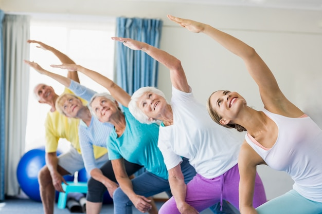 Instructor realizando yoga con personas mayores