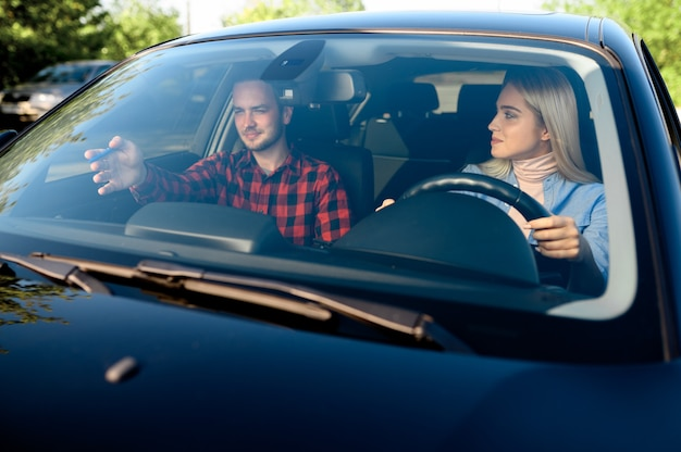 Instructor de señora y hombre en coche, autoescuela. hombre enseñando a una mujer a conducir un vehículo.