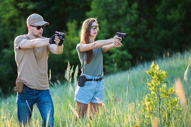 El instructor de tiro le enseña al reincidente cómo manejar un arma.