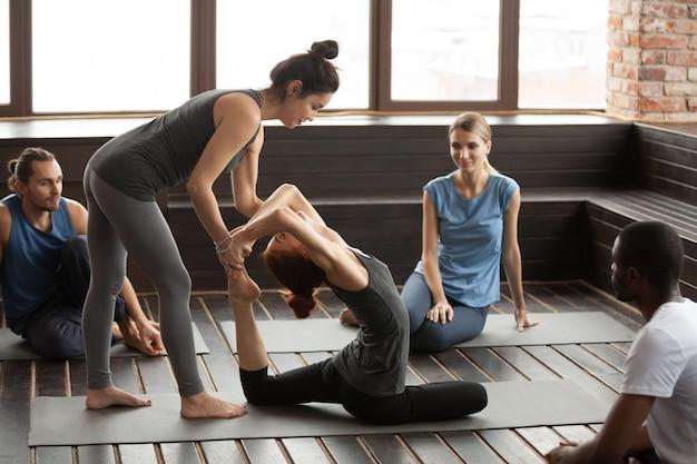 Instructor de yoga femenino ayudando a la mujer haciendo ejercicio en grupo tra