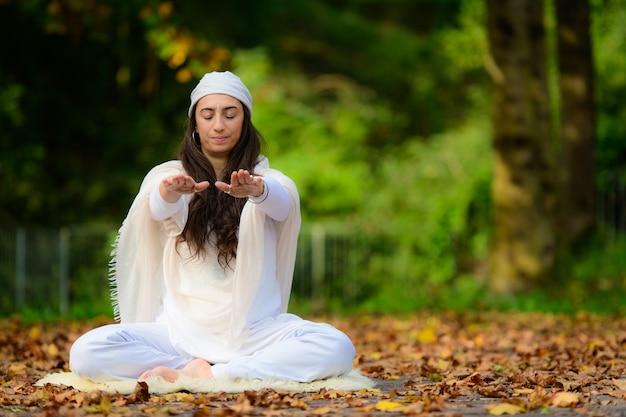Instructor de yoga practica ejercicios entre las hojas de otoño en el parque