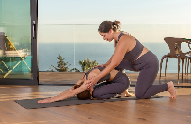 Instructor de yoga de tiro completo ayudando a mujer