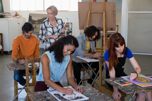 Instructora examinando estudiantes pintando en la mesa