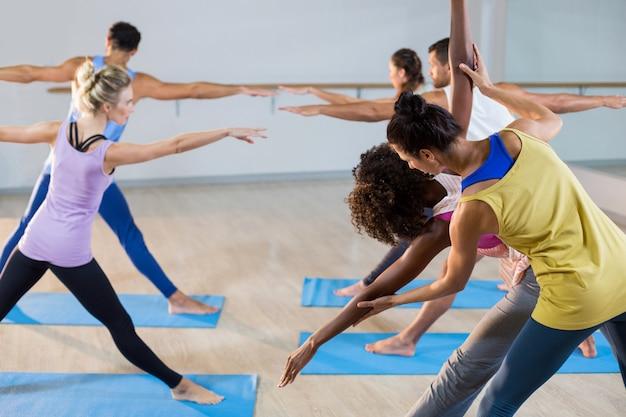 Instructora de yoga ayudando al estudiante con una pose correcta