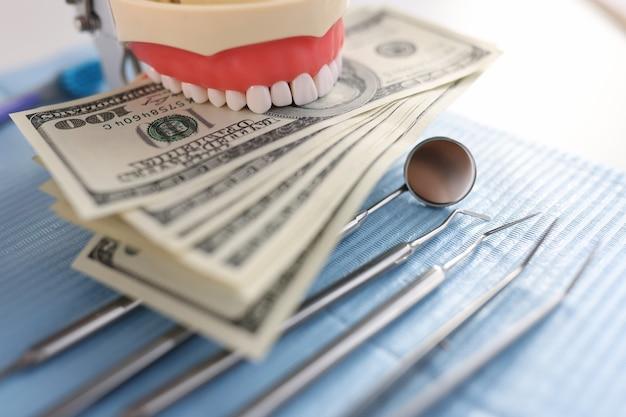 Instrumento de mandíbula artificial dental y billetes de cien dólares en el tratamiento dental del escritorio del dentista