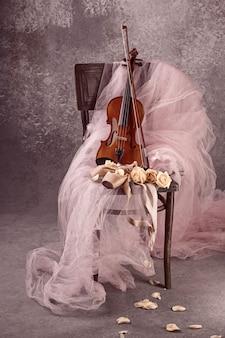 Instrumento de violín vintage con rosas y zapatillas de ballet