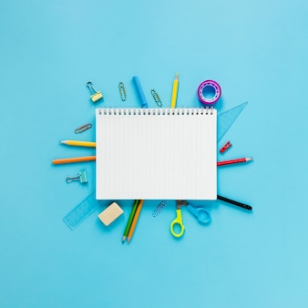 Instrumentos escolares y de oficina sobre fondo cian
