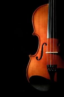 Instrumentos musicales de la orquesta del violín del primer en fondo negro