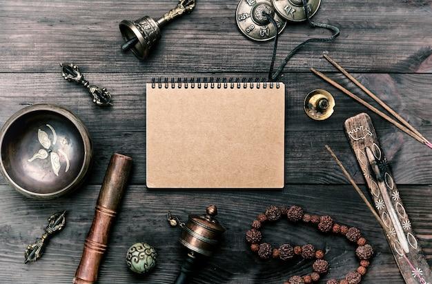 Instrumentos musicales religiosos para meditación y medicina alternativa, cuaderno en blanco con hojas marrones.