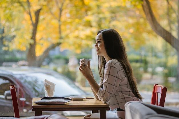 Integración de musulmanes en europa. hermosa joven musulmana adopta la cultura europea. una joven musulmana sentada en un café sin hiyab.