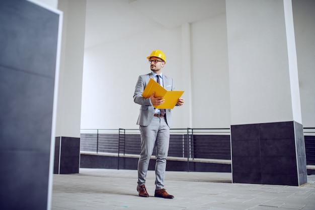 Integral del arquitecto masculino sin afeitar con clase hermoso en traje y con el casco en la cabeza que camina al aire libre con la carpeta en manos.