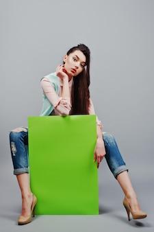 Integral de la muchacha hermosa que se sienta, sosteniendo la bandera verde en blanco del tablero de publicidad, sobre fondo gris. tu texto aqui