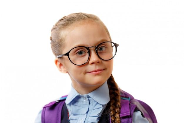 Inteligente joven colegiala con gafas sobre fondo blanco