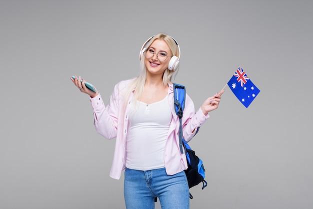 Inteligente joven mujer rubia en auriculares satisfechos con el aprendizaje de idiomas durante los cursos en línea con el teléfono inteligente, sonriente estudiante haciendo la tarea, buscando información a través del teléfono móvil