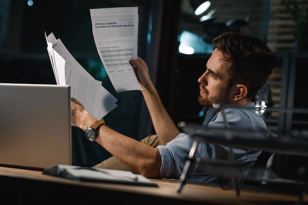 Inteligente trabajando hasta tarde con papeles