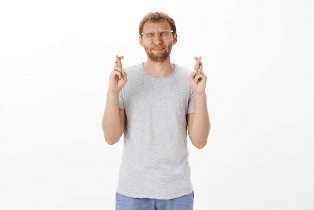 Intenso macho adulto lindo preocupado con cerdas en vasos cerrando los ojos frunciendo los labios y cruzando los dedos para tener buena suerte mientras espera que el plan funcione