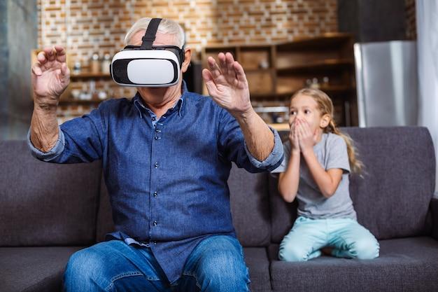 Intentalo. agradable anciano con gafas vr mientras está sentado en el sofá con su nieta