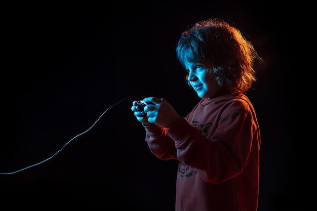 Intenté jugar videojuegos. retrato de niño caucásico sobre fondo oscuro de estudio en luz de neón. preciosa modelo rizada. concepto de emociones humanas, expresión facial, ventas, publicidad, tecnología moderna, gadgets.