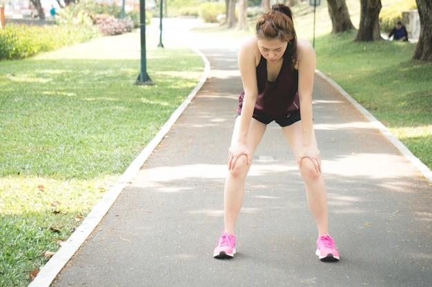 Intento asiático de la sensación de la mujer del deporte después de correr en parque