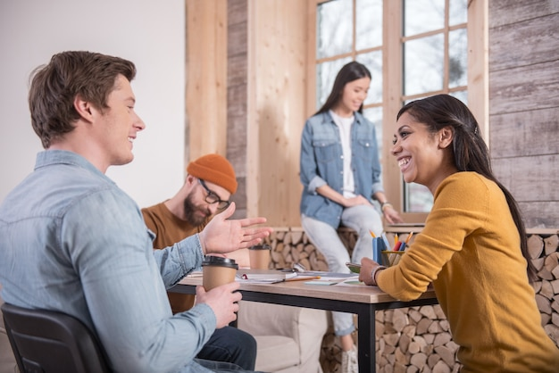 Interacción agradable. gente agradable encantada positiva sentados juntos y tener una conversación mientras se trabaja